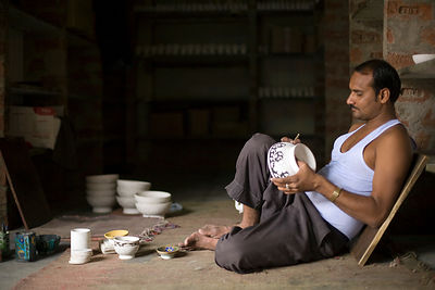 India - Rajasthan - A Potter paints a clay bowl at a factory in Sanganer