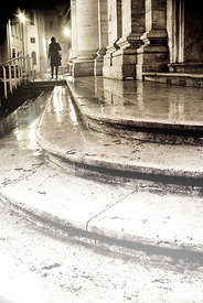 An atmospheric image of a lone woman walking down down some steps in the rain, at night time, Rome, Italy