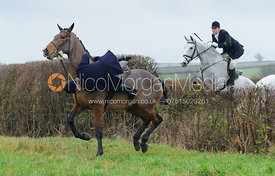 Emily Clark jumping a hedge behind Waterloo Lodge