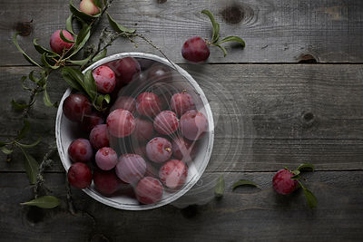plums just picked from the tree spilling out of a rustic white ceramic bowl sitting on a wood table