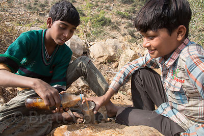 Boys herding goats make chai tea by filling a plastic water bottle with water from a creek, milk from their goat, and tea fro...