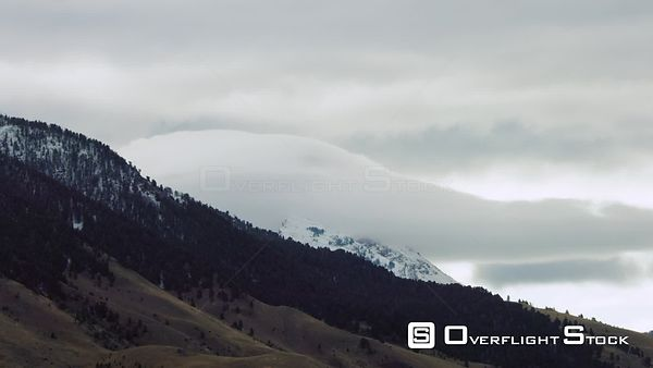 Low hanging clouds drape over the snowcapped Madison mountain range in Southwestern Montana