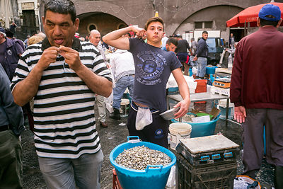 A young trader stretches whilst selling clams at the Mercato della Pescheria Market