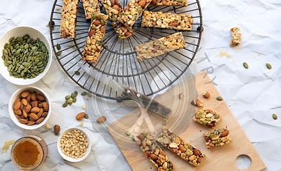 Honey nut bars with seeds and nuts in small bowls.