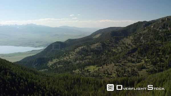 A lush spring green Madison Valley sits below the Madison mountain Range and the Gravelly mountain Range, between Yellowstone...