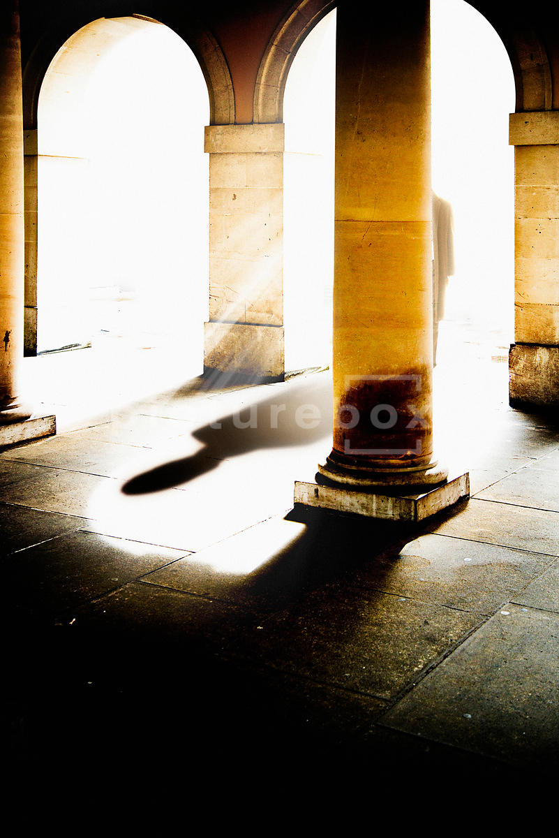 An atmospheric image of the shadow of a mystery man, coming through the cloisters of an old building.