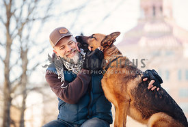 german shepherd licking face of stylish man downtown