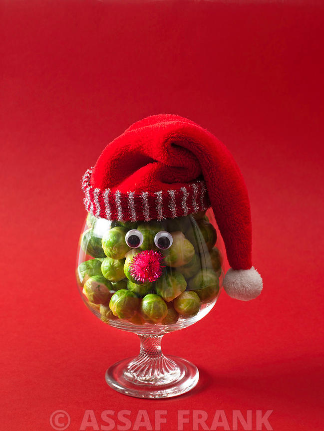 Santa face on a wine glass filled with brussel sprouts