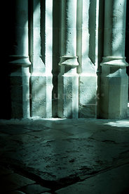 An atmospheric image of sunlight coming through A church window and falling onto some impressive columns.