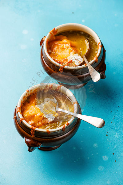 Authentic French Onion soup with dried bread and cheddar cheese in bowl on blue background