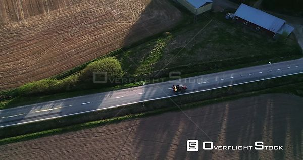 Tractor on the Road, Aerial Tracking View Following a Fertilizer Machine Leaving the Field and Driving on a Asphalt Route, on...