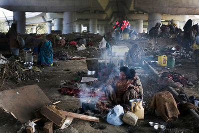 India - New Delhi - A homeless mother cooks breakfast  by the railway tracks where her family lives