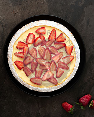 Strawberry and custard dessert cake on a black plate.