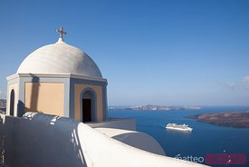 Cruise ship under famous church in Santorini Greece