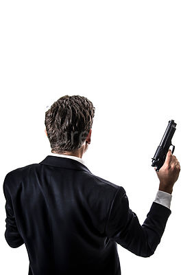 A mystery man in a suit, holding a gun – shot from above.