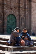 Two women sitting on steps to cathedral in Puno, Peru