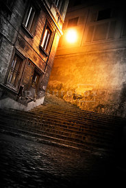 An atmospheric image of some steps in a dark alleyway dimly lit by a streetlight.