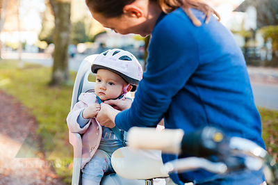 Mother and daughter riding bicycle, baby wearing helmet sitting in children's seat