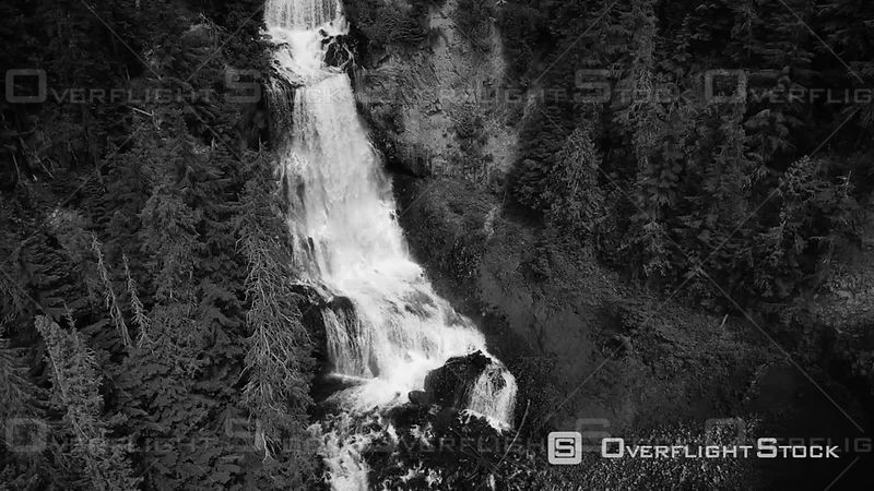 Monochrome drone cinematography panning down on cascading waterfalls in Canada