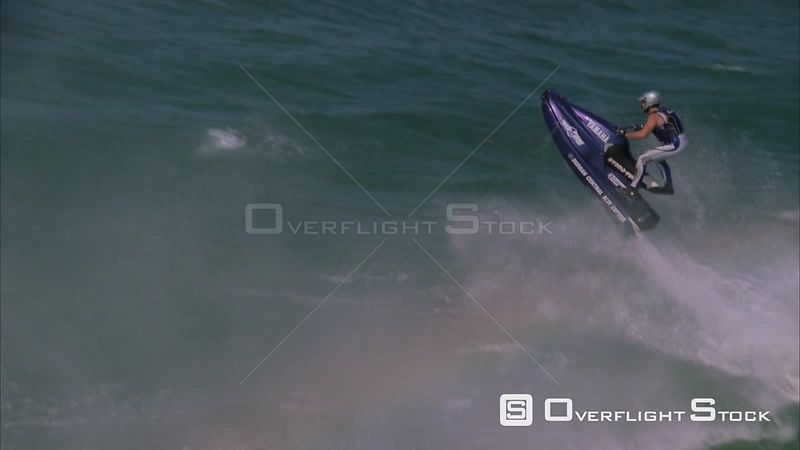 Slow motion aerial shot of a jetskier performing a trick in the air as he ramps a wave. . South Africa