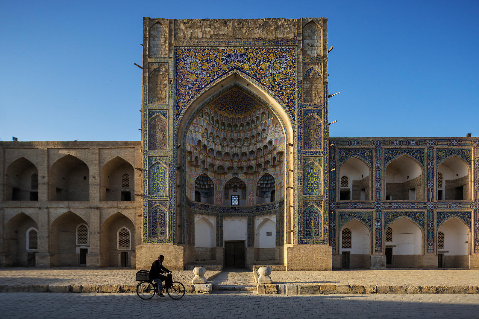 Man Riding a bicycle in front of the Abdul Azizxon Masdrassah