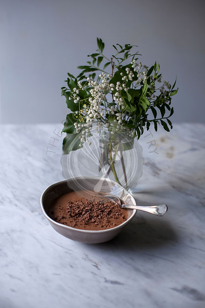 Chocolate mousse sprinkled with grated dark chocolate in a smal bowl on white marble table