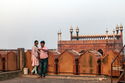A couple on the roof of the Jama Masjid in Old Delhi look at a mobile telephone
