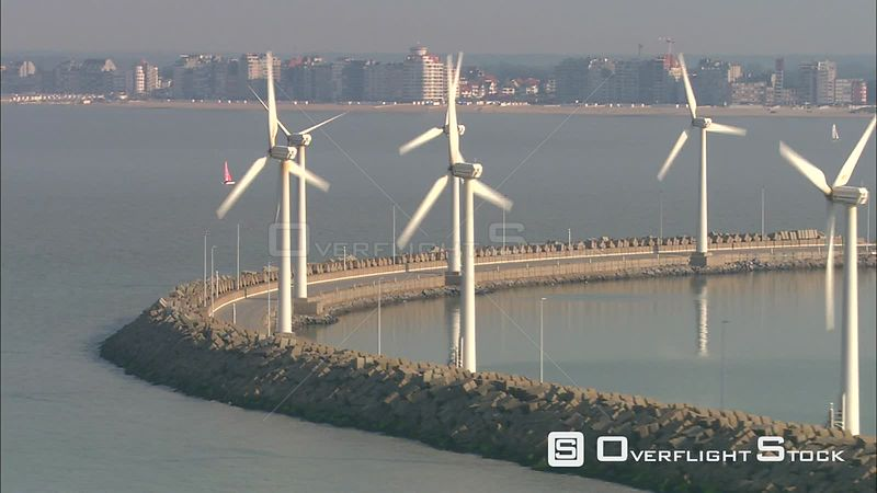 Wind turbines along a breakwater at harbor in Zeebrugge, Belgium city skyline in background
