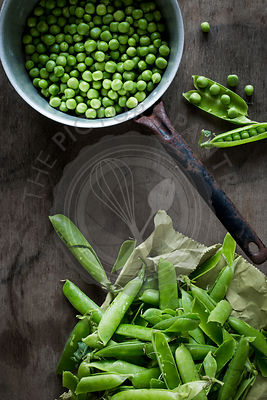 Peas in vintage colander and pods on paper bag on wooden table. Top view