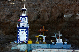 Miniature clock tower and shrine for dead fisherman next to harbour , Pisagua , Region I , Chile