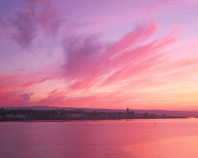 A peaceful scene viewed from Newlyn Pier as a sweeping cloud formation starts to glow in the pre-dawn light.