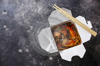 Udon noodles stir-fried with Tiger shrimps Asian food in box Take out food on dark background copy space