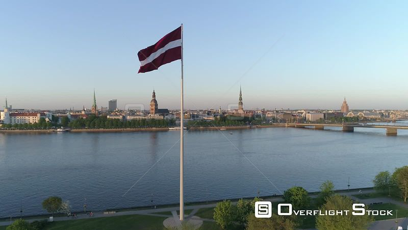 Aerial drone shot of a large flag of Latvia with Riga Old Town in background