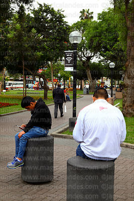 Young men surfing internet on mobile phone in public wifi area in Parque Kennedy, Miraflores, Lima, Peru