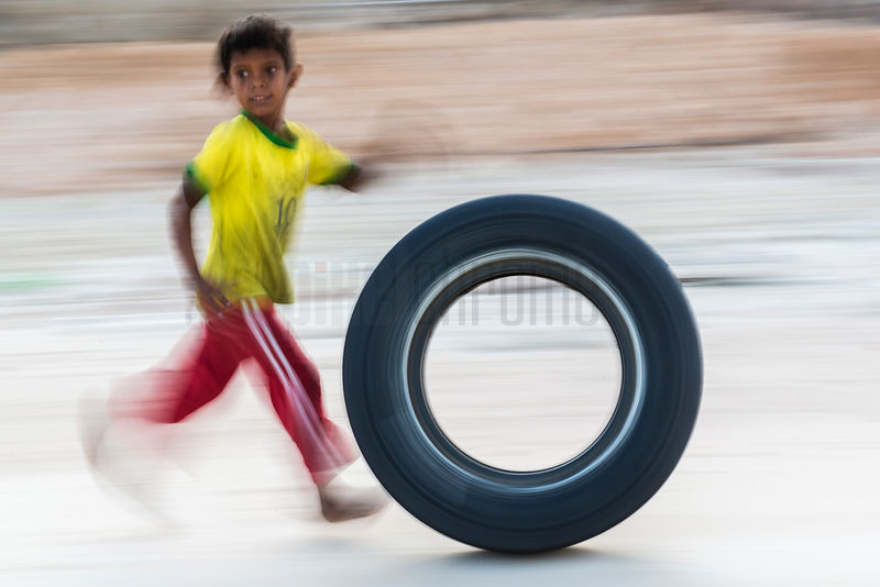 Young Boy Wheeling a Tyre