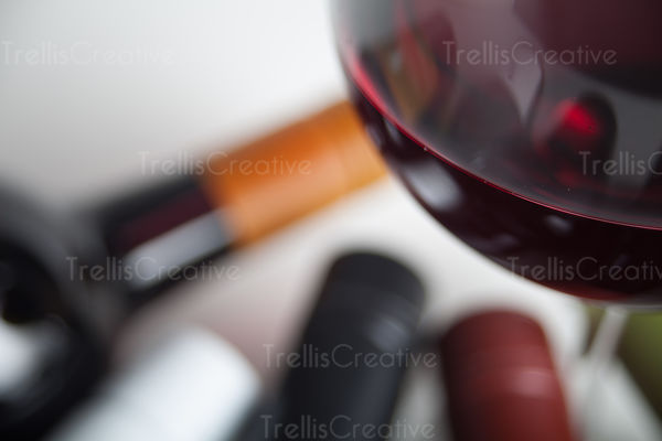 Close-up of red wine glass with wine bottles in background