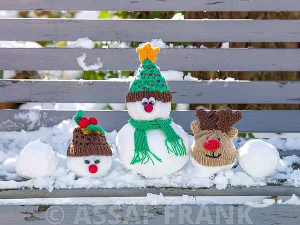 Christmas snowman figurines on bench covered with snow