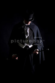 An image of a Victorian man in a cloak, standing, In the darkness.