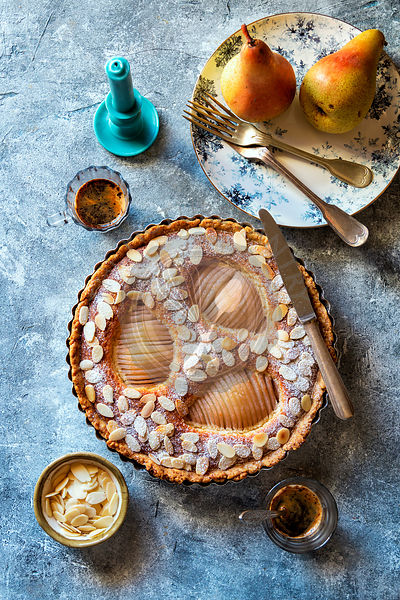 Frangipane pear tart sprinkled with toasted almond flakes with two cups of coffee on the table