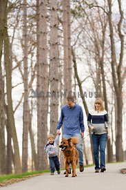 family with child walking dog in a forest