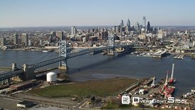 Aerial approach to Philadelphia across edge of Camden and the BeNJamin Franklin Bridge.