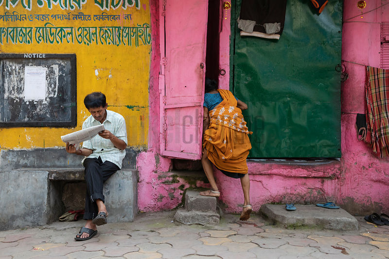 Man Reads a Newspaper Next to a Pink Wall