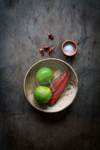 Wooden bowl with ingredients for chili paste on wooden tabletop. Top view