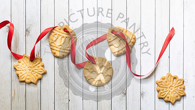 Christmas cookies threaded on red ribbon.