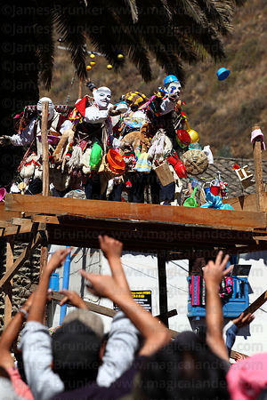 Kapac Qolla dancers distributing gifts to crowd from raised platform at Virgen del Carmen festival , Paucartambo , Peru