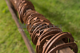 A row of rusted horsehoes arranged on a fence railing at a stable
