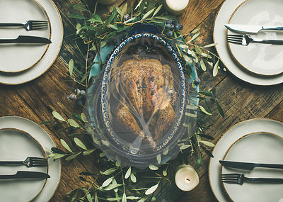 Flat-lay of whole roasted chicken in tray for Christmas eve celebration, plates and candles over rustic wooden background