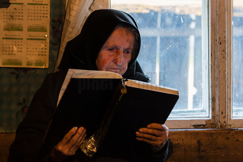 Portrait of Maria Munganu, 85, in her 200 Year Old Home Reading a Bible