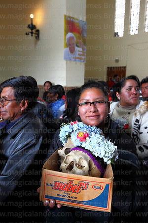 Woman with her skull in front of poster of Pope Francis in church during mass, Ñatitas festival, La Paz, Bolivia