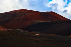 Rich red colours of volcanic dust under the clouds in Timanfaya national park, Lanzarote